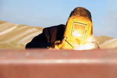 Welder in the production on the field. Welding in the opencast mine stock photography