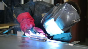 Welder in protective clothing working with metal, welding metal. Slow motion.