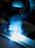 Welder with protective equipment in factory Stock Photos