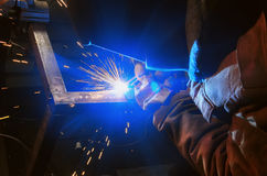 Welder in a protective mask in a dark shop floor weld metal parts. Sparks flyng Royalty Free Stock Photos
