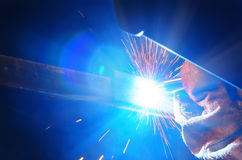 Welder in a protective mask in a dark shop floor weld metal parts. By welding sparks fly in different directions. Welder in a protective mask in a dark shop Royalty Free Stock Image