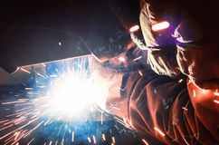 Welder in a protective mask in a dark shop floor weld metal parts. By welding sparks fly in different directions. Welder in a protective mask in a dark shop Stock Photos
