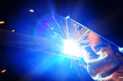 Welder in a protective mask in a dark shop floor weld metal parts. By welding sparks fly in different directions. Welder in a protective mask in a dark shop Stock Images