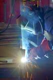 Welder with protective mask welding metal Stock Image