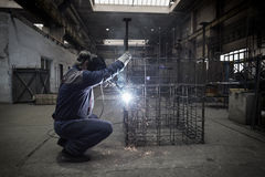 Welder with protective mask welding reinforcement bars Royalty Free Stock Images
