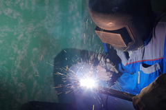 Welder in protective suit and mask welds Royalty Free Stock Photo