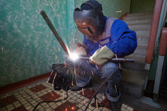 Welder in protective suit and mask welds metal pipes Stock Photos