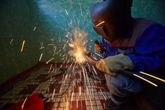 Welder in protective suit and mask welds metal pipes Royalty Free Stock Photography
