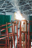Welder in protective suit welds steel frame Royalty Free Stock Photos