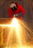 Welder in red creates huge orange sparks stock images