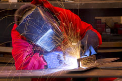 Welder in red overalls creates sparks.    Royalty Free Stock Photo