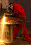 Welder in red overalls cuts metal. Royalty Free Stock Photography