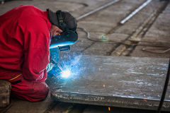 Welder in red suit with proper protection Stock Images