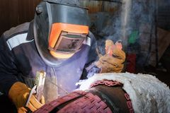 Welder in the shop weld sample from the tube with concomitant he Royalty Free Stock Photo