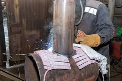 Welder in the shop weld sample from the tube with concomitant he Stock Photo