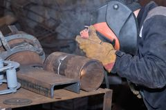 Welder in the shop weld sample from the tube for passing of cert Royalty Free Stock Photo