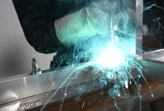 Welder with sparks. Arcing in a cyan light Royalty Free Stock Images
