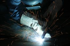 Welder and Sparks. Worker in a welding mask welding with red sparks flying Stock Images