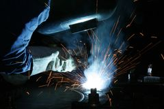 Welder and sparks. Welder in mask with red sparks flying Stock Photos