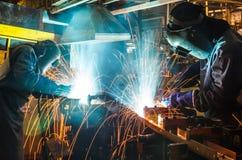 Welder svetsande automatisk del i en bilfabrik Arkivbild