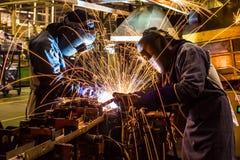Welder svetsande automatisk del i en bilfabrik Fotografering för Bildbyråer