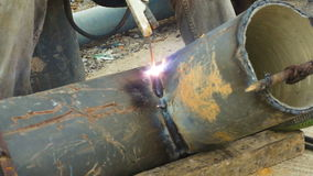 Welder uses arc welding pipe metal on site. stock video