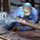 Welder Using the Shielded Metal Arc Process. KAOHSIUNG, TAIWAN -- JANUARY 1, 2015: An unidentified welder works on an object for the Kaohsiung Iron and Steel Stock Photo