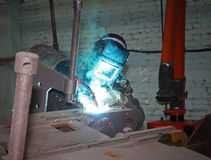 A welder wearing a mask at work Stock Images