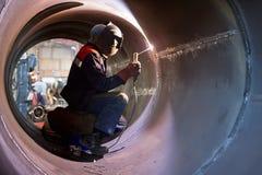 Welder weld root weld from inside of big pipe Stock Images