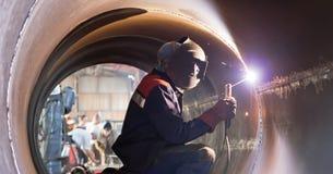 Welder weld root weld from inside of big pipe Stock Photos