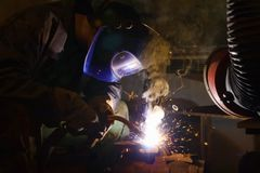 Welder welding. Welder with welding helmet working, sparks and smoke around him Royalty Free Stock Images