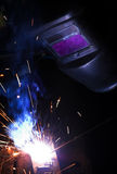 Welder Welding. Welder with protective mask welds metal and sparks Stock Photo