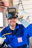 Welder with welding device in metal workshop. Looking into camera Stock Photography