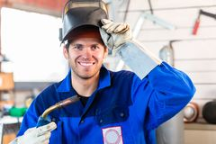 Welder with welding device in metal workshop. Looking into camera Stock Image