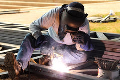 Welder welding metal with bright sparks. Welder welding steel  metal with bright sparks on construction site Stock Image