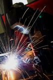 Welder welding a metal part. In an industrial environment. Blue light on dark background Stock Images