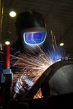 Welder welding a metal part. In an industrial environment, sparks flying, acetylene fumes Stock Images