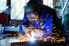 Welder welding metal in workshop with sparks. Welder bonding metal with welding device in workshop, lots of sparks to be seen, he wears welding googles Royalty Free Stock Photo