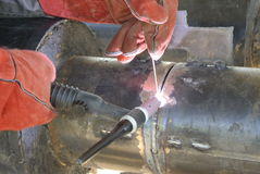 A welder welding a pipe Royalty Free Stock Photos