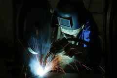Welder and welding sparks. A view of a worker in protective welding gear, welding with sparks flying in a dark workplace Royalty Free Stock Images