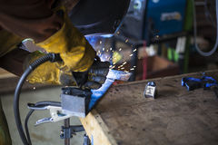 Welder welding steel base for new stool. Royalty Free Stock Photos