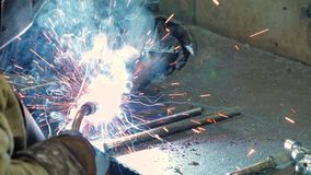 Welder in the mask welds. Welder welding steel and iron in extremely slow motion. The welder uses a mask to protect his eyes from sparks. concept: handmade stock video footage