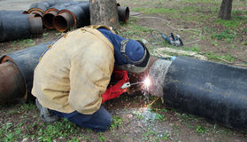 Welder Welding Two Big Pipes. Welder assembling pipes for hot water and steam heating Stock Photos