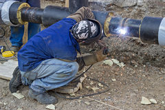 Welder welding underground steel pipe kneels on ground Stock Photography