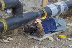 Welder welding underground steel pipe lying on ground 3 Stock Image