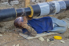 Welder welding underground steel pipe lying on ground 4 Stock Photos