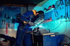 Welder welding with welding mask and torch in workshop Stock Images