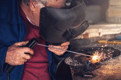 Welder welding in workshop. Mature welder welding two metal scraps in workshop Royalty Free Stock Photography
