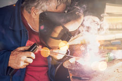 Welder welding in workshop. Mature welder welding two metal scraps in workshop Stock Photo