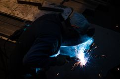 Welder is welding at workshop. Welder is welding two pieces of metal carefully at the workshop. Horizontal photo Stock Image